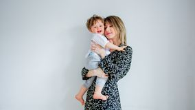 Mother and son on a white wall background at home royalty free stock images