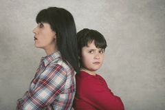 Mother and son who are angry. Against gray background stock image