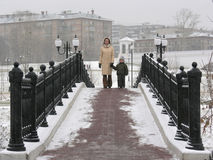 Mother with son on winter bridge. Torch stock photos