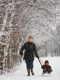Mother with son in winter park with sled Stock Images
