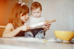 Mother with son. A young and beautiful mom is preparing food at home in the kitchen, along with her little son royalty free stock image