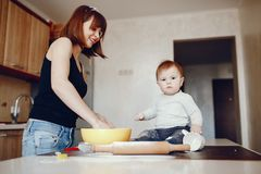Mother with son. A young and beautiful mom is preparing food at home in the kitchen, along with her little son royalty free stock photography