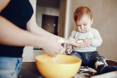 Mother with son. A young and beautiful mom is preparing food at home in the kitchen, along with her little son royalty free stock photos