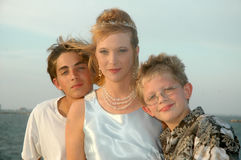 Mother and Sons. Beautiful mother with her two sons on her wedding day. Sitting by the sea. Summer day with a breeze Royalty Free Stock Photo