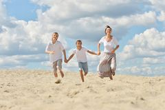 Mother and sons. On a beach against the sky stock photography