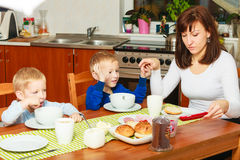 Mother and sons boys kids children eating breakfast together Stock Photography