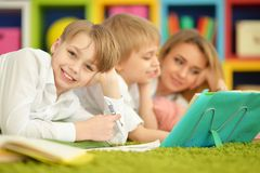 Mother and sons doing homework. While lying on floor in room Royalty Free Stock Images