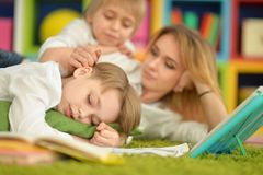 Mother and sons doing homework. While lying on floor in room Stock Photography