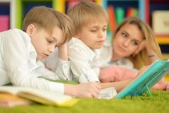 Mother and sons doing homework. While lying on floor in room Stock Images