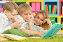 Mother and sons doing homework. While lying on floor in room Royalty Free Stock Image