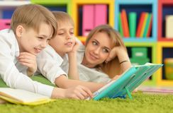 Mother and sons doing homework. While lying on floor in room Stock Image