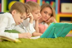 Mother and sons doing homework. While lying on floor in room Royalty Free Stock Photo