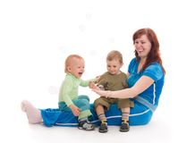 Mother with sons enjoy with coloured soap bubbles. Young mother with her sons enjoy with coloured soap bubbles over white background Royalty Free Stock Photo