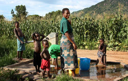 Mother and sons by a fountain in Africa. A family get water from a pump fountain in Malawi, Africa. Tough in the African continent the water supply is today stock images