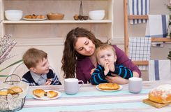 Mother and sons having breakfast. Mother and two children in the kitchen having breakfast. Happy family time. Mother and sons having breakfast. Concept of happy Stock Photo