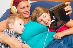 Mother and sons with headphones listen to music hugging each oth Royalty Free Stock Image
