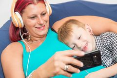 Mother and sons with headphones listen to music hugging each oth Stock Photos