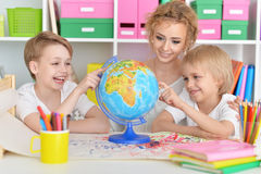 Mother and sons looking at globe. Mother and sons looking at colorful world globe Stock Images