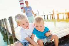 Mother with sons on the pier, lighthouse, sunny summer day Stock Images