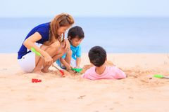 Mother and sons are playing on tropical beach Royalty Free Stock Photo