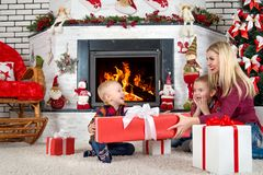 Merry Christmas and Happy Holidays!Mother and sons sitting by the fireplace and open Christmas gifts from Santa. royalty free stock photography