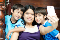 Mother and sons taking selfie with mobile Royalty Free Stock Image