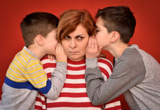 Mother and sons. Sons whispering secret into ears of angry mother Stock Photo