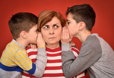 Mother and sons. Sons whispering secret into ears of angry mother Stock Image