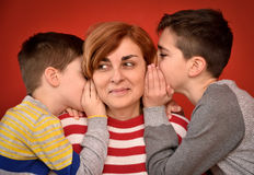 Mother and sons. Sons whispering secret into ears of smiling mother Royalty Free Stock Image