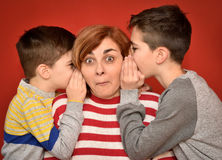 Mother and sons. Sons whispering secret into ears of surprised mother Stock Image