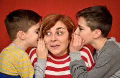Mother and sons. Sons whispering secret into ears of surprised mother Royalty Free Stock Image