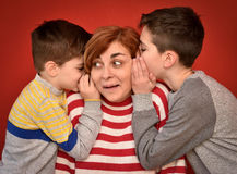 Mother and sons. Sons whispering secret into ears of surprised mother Stock Photo