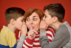Mother and sons. Sons whispering secret into ears of surprised mother with index finger on her mouth Royalty Free Stock Image