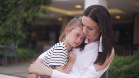 Little girl crying sitting on mother