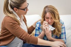 Mother soothes sad teen daughter crying Stock Photography