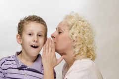 Mother speaks to her son. Head-and-shoulder view of blonde mother sideways whispers in the ear of her 7-year old son with quietly against white background Stock Images