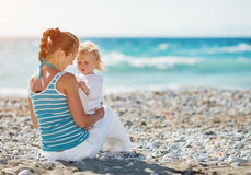 Mother spending time with baby on beach Stock Photos