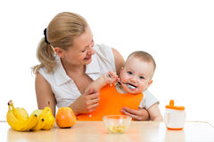 Mother spoon feeding baby boy Royalty Free Stock Images