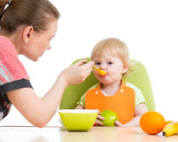 Mother spoon feeding baby girl Stock Image