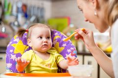 Mother spoon feeding child toddler Stock Photography
