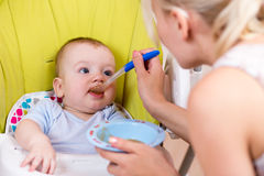 Mother spoon feeding her baby boy Royalty Free Stock Images