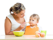 Mother spoon feeding her baby girl Stock Photo