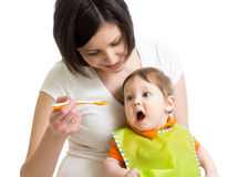 Mother spoon feeding her baby Stock Images