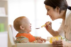 Mother spoon-feeding her child boy. Mother spoon feeding her baby boy. e view portrait of young women giving food to kid son Stock Images