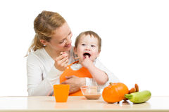 Mother spoon feeding her cute baby boy Stock Photos