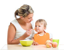 Mother spoon-feeding her cute baby girl Royalty Free Stock Photo