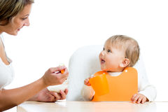Mother spoon feeding her funny baby girl Stock Photos