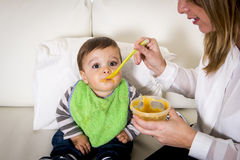 Mother with spoon porridge feeding sweet little son in messy bib mush stains Stock Images