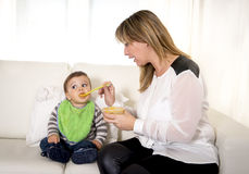 Mother with spoon porridge feeding sweet little son in messy bib mush stains Stock Photos