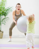 Mother in sportswear playing with baby at gym Stock Images